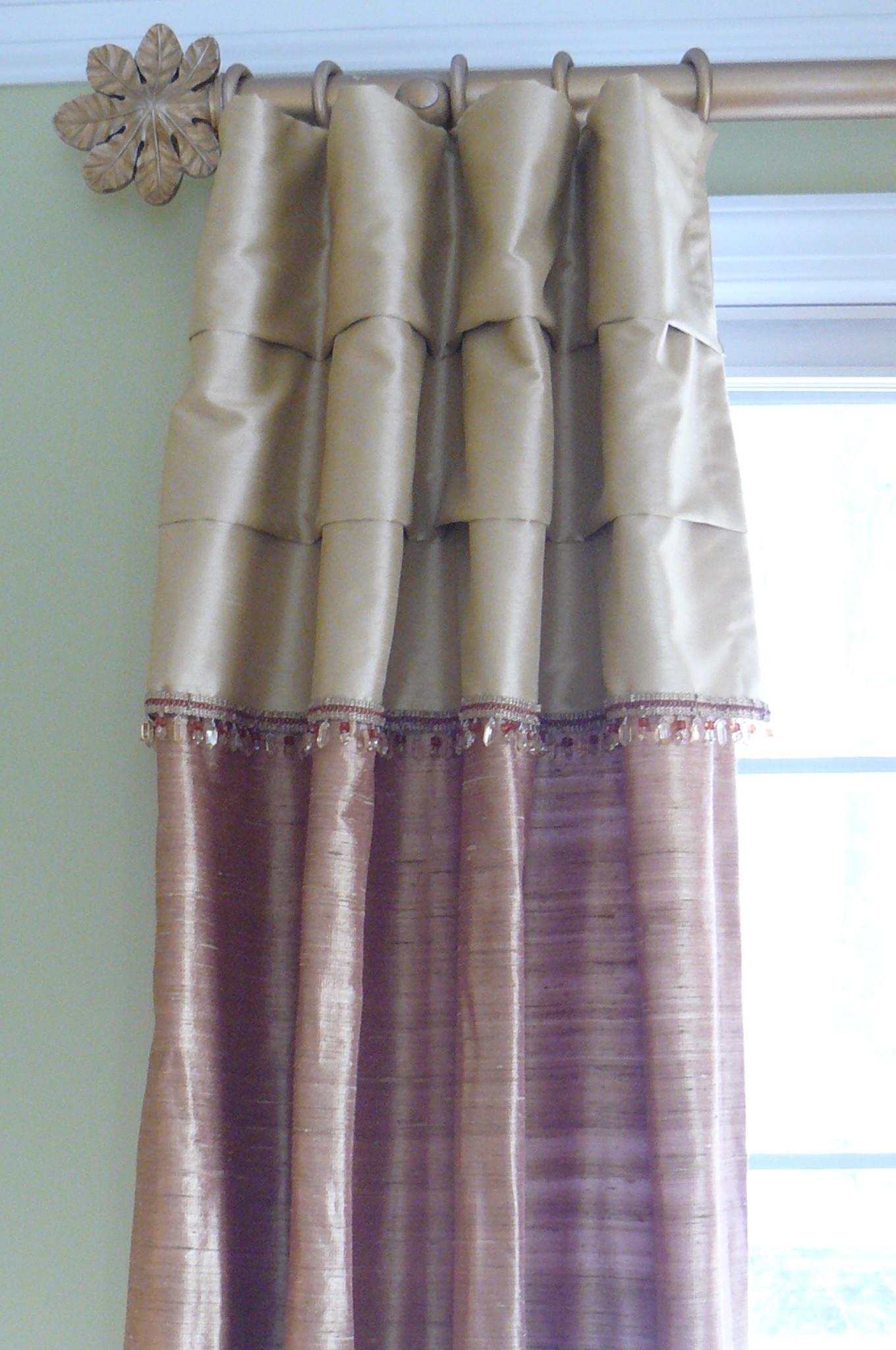 Silk panel with attached valance and bead trim on decorative for living room area