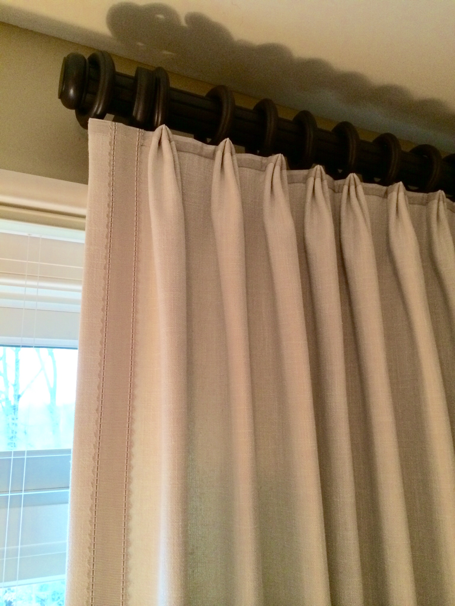 Top pleat panels on decorative rod with accent banding and fabric accent on top