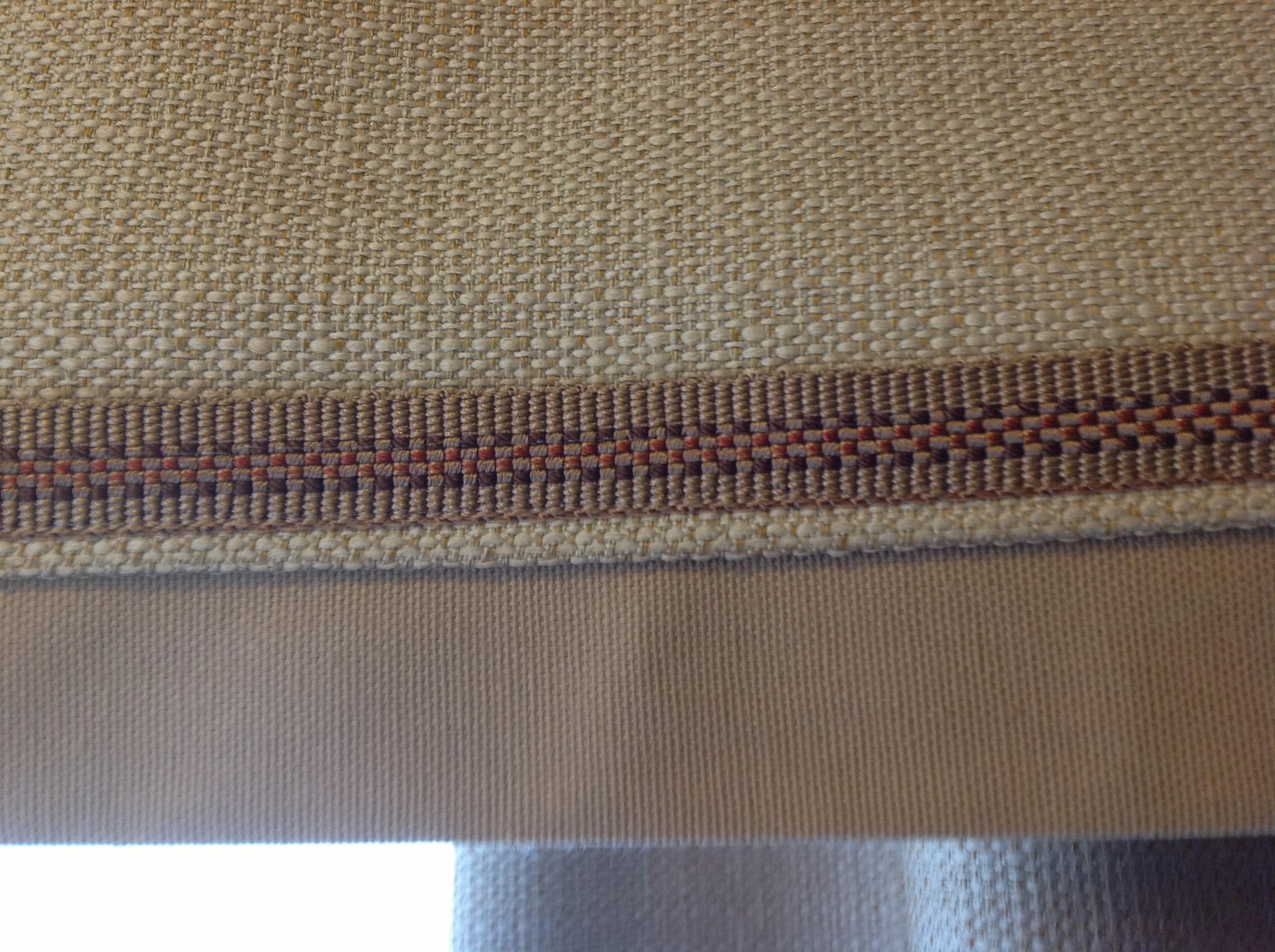 close up detail of box pleat valance installed over draperies