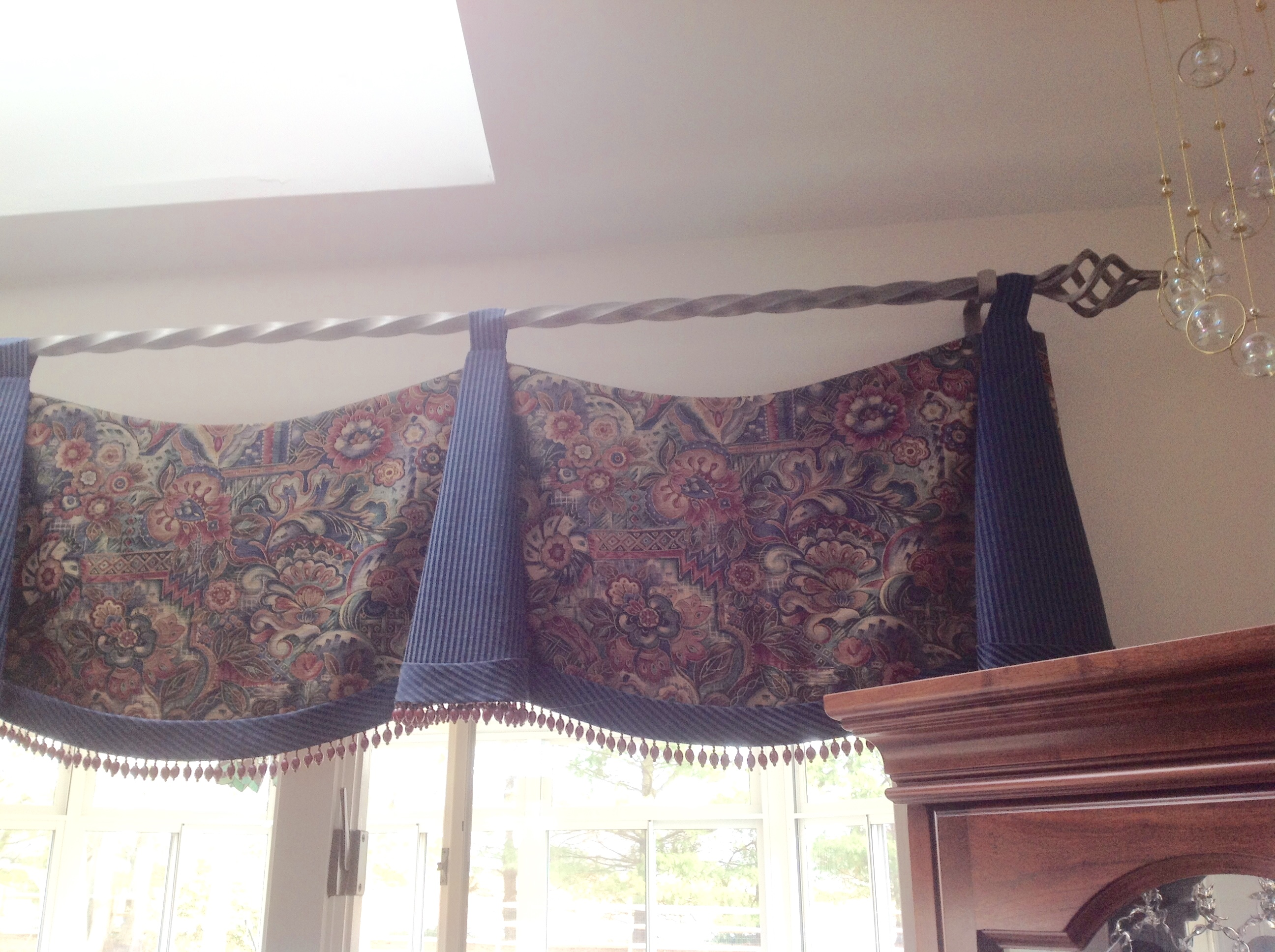 Scalloped valance with bells and bead trim on decorative rod over kitchen window